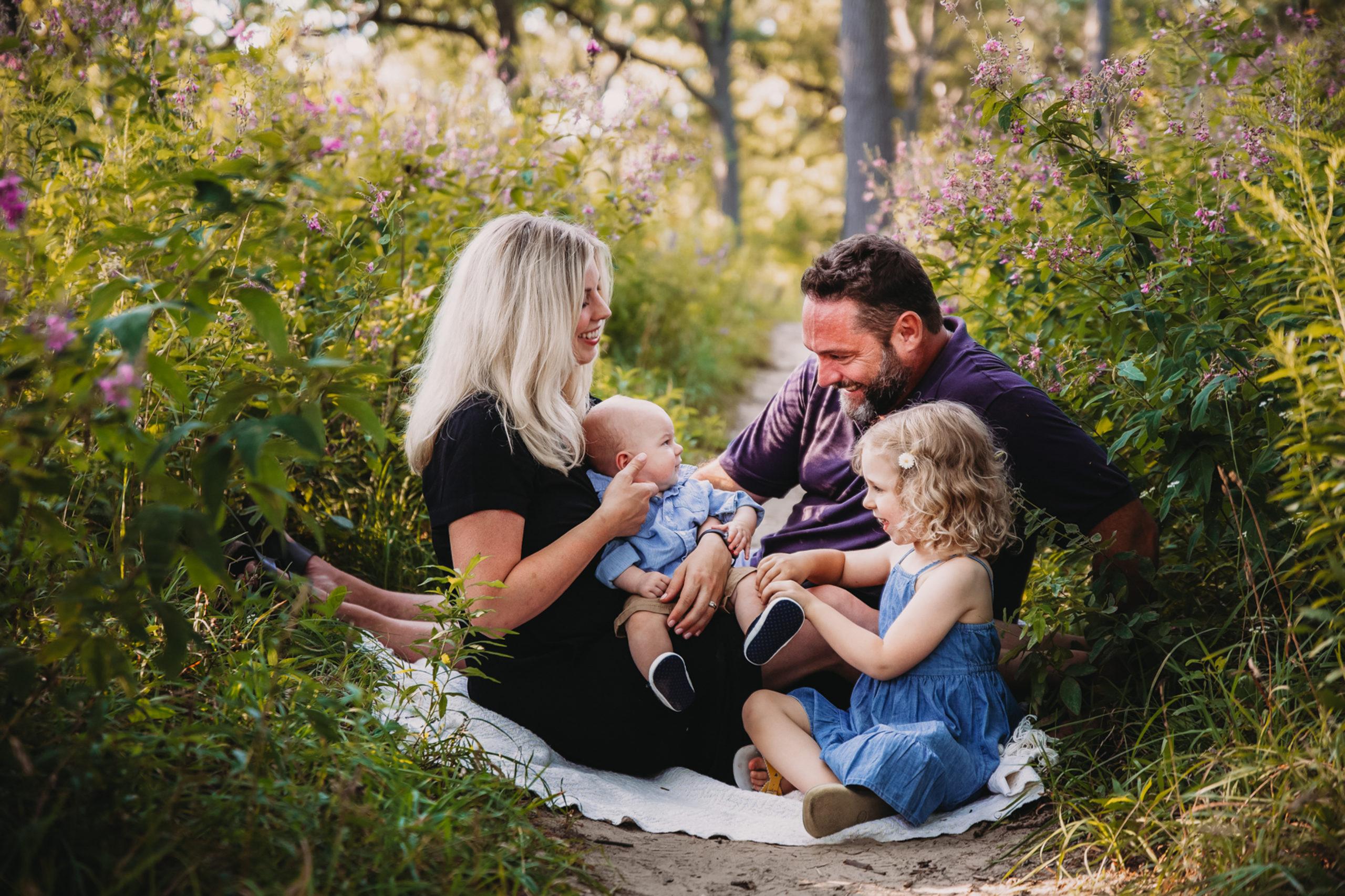 family portrait guide- family posing on blanket in forest